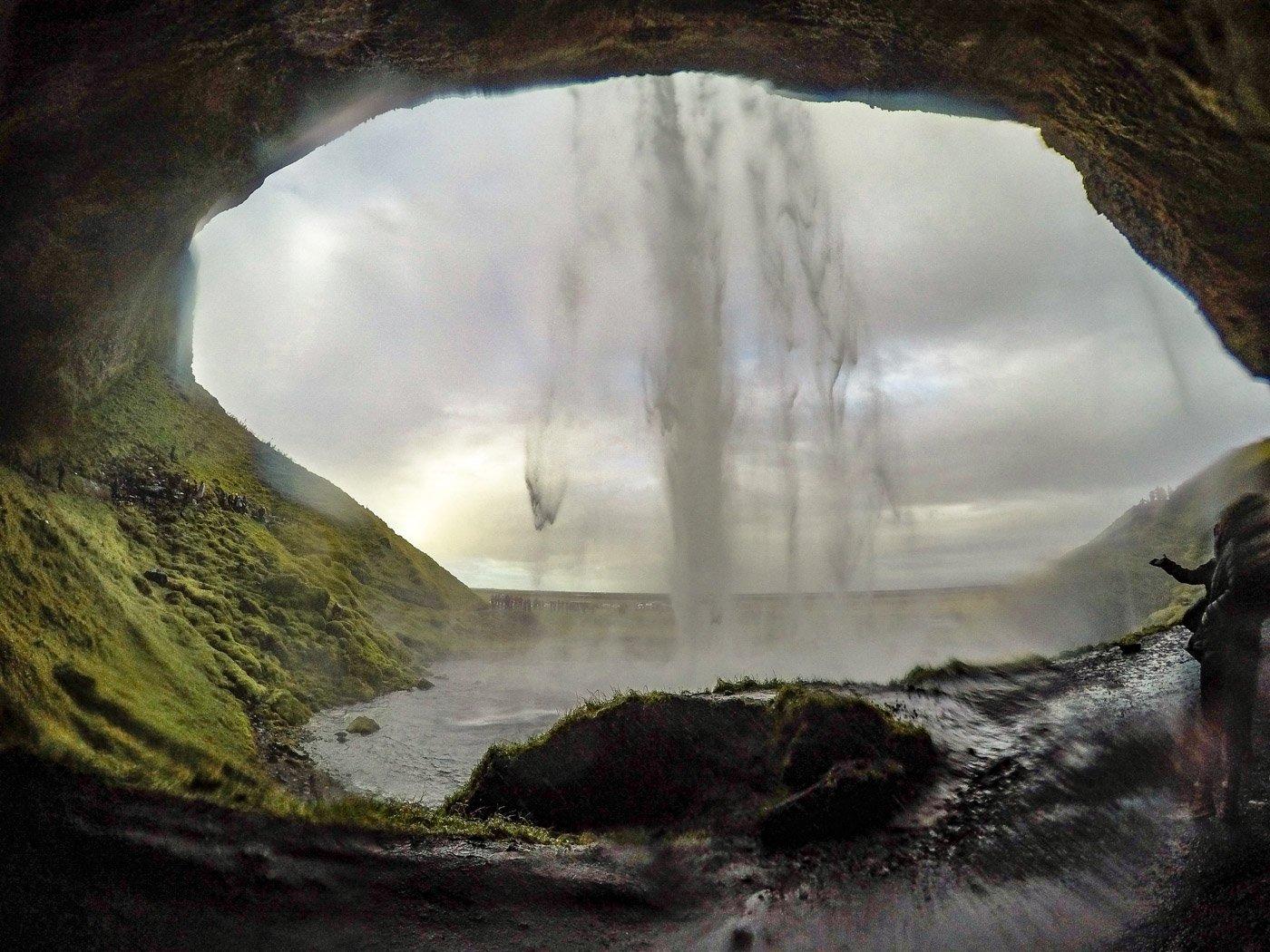 Walking behind Seljalandsfoss waterfall on the south coast of iceland